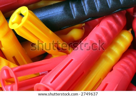 Macro photo of brown, red, and yellow nylon wall plugs of various sizes - stock photo