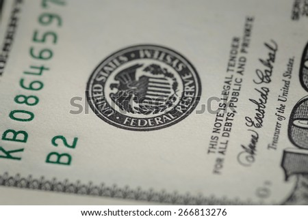 macro photo of federal reserve system symbol on hundred dollar bill - stock photo