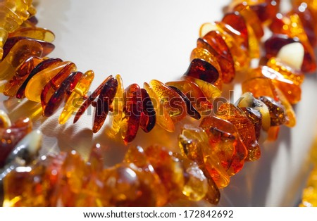 Macro photo of orange amber beads on white background - stock photo