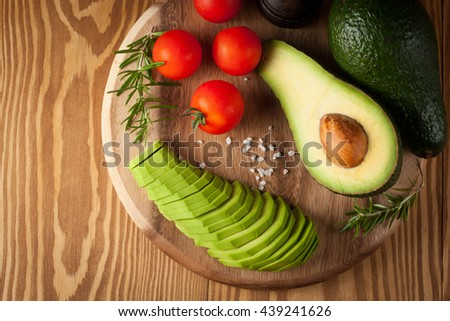 macro photo of sliced avocado with tomatoes on a cutting board on wooden background. Healthy organic food concept. - stock photo
