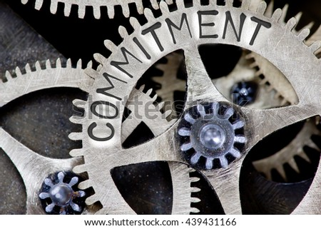 Macro photo of tooth wheel mechanism with COMMITMENT concept letters - stock photo