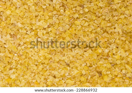 Macro photograph of raw, light-coloured, fine-ground burghul or bulgur wheat, a staple of the Middle Eastern diet and considered a health food in the West as it has a low glycemic index - stock photo