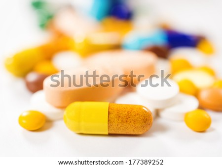 Macro shoot and selective focus on the front yellow pill - stock photo
