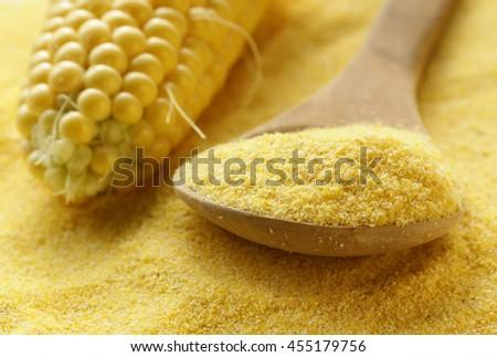 macro shot corn flour in a wooden spoon, soft focus - stock photo