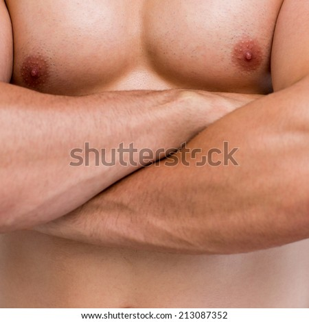 Macro shot mid section of a shirtless muscular man with arms crossed