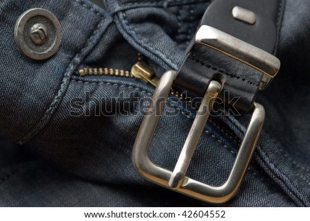 Macro shot of a jeans's zipper and a belt above it