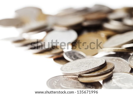 Macro shot of a large quantity of unrecognizable coins (except for one that appears to be Swiss) stacked in chaos over white background. Very shallow depth of field.