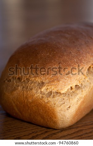 Macro shot of a loaf of homemade whole wheat bread on a wooden table