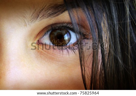 Macro shot of a surprised child's brown eye and hair - stock photo