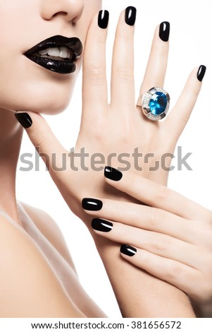 Macro shot of a woman's lips and nails painted bright color black. Person holds in mouth blue stone. - stock photo