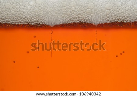 Macro shot of amber beer with bubbles and head - stock photo