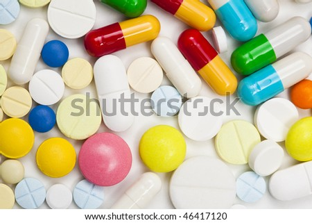 Macro shot of assorted colored pills and capsules on white back ground