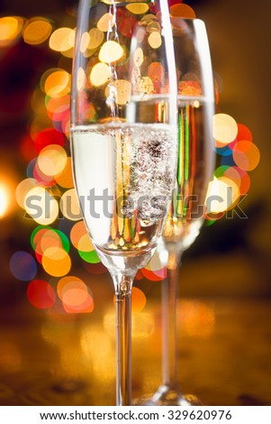 Macro shot of champagne poured in glasses against Christmas lights - stock photo