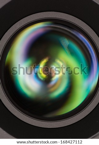 Macro shot of front element of a camera lens with beautiful color lights reflections  - stock photo