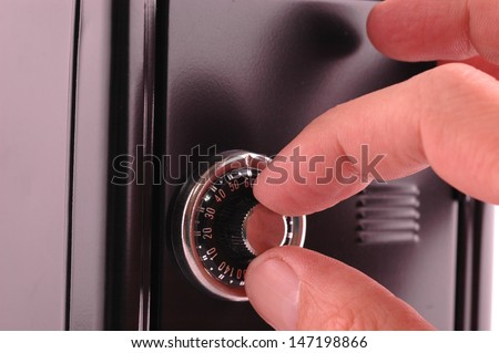 Macro shot of hand searching security code of safe, blue tone - stock photo