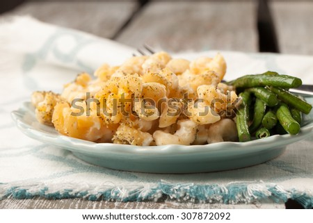 Macro shot of healthy whole grain macaroni and cheese with pureed cauliflower sauce and stir-fried Asian green beans on a weathered barn wood table - stock photo