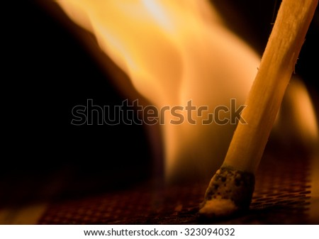 Macro shot of lit match shows flame coming from head of match - stock photo