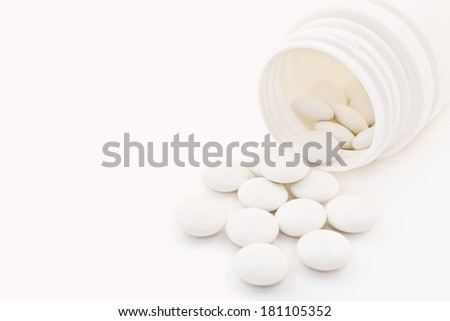 Macro shot of medical tablets with vial on white background - stock photo