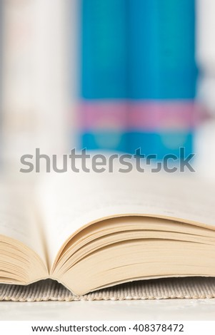 Macro shot of open book in library. Selective focus. Vertical view. - stock photo
