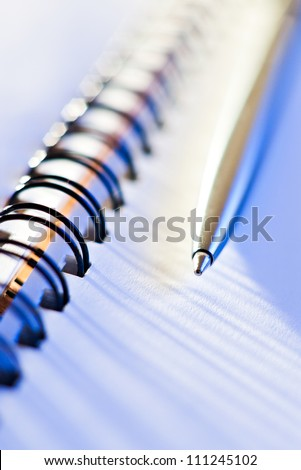 macro shot of pen and business note-book in blue light - stock photo