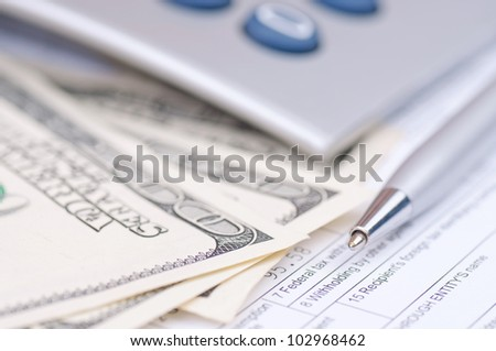 Macro shot of pen, hundred-dollar bills and cropped calculator - stock photo
