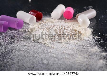 Macro shot of powder by open pills - stock photo