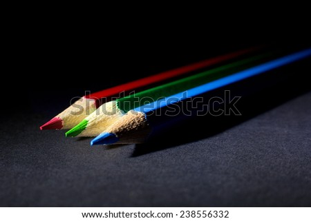 Macro Shot of Red, Green and Blue Sharpened Colorful Pencils Against Black Background. Instruments for writing or drawing, consisting of a thin stick of graphite enclosed in a long thin piece of wood  - stock photo