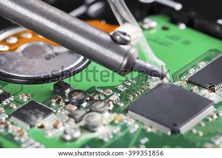 macro shot of soldering iron and circuit board - stock photo