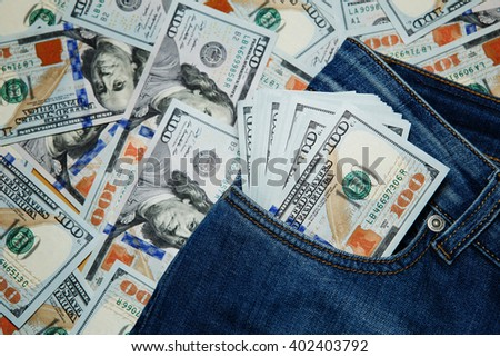 Macro shot of trendy jeans with american 100 dollars bills on its pocket. 100 dollar bill sticking out from a blue jean pocket - stock photo