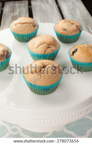 macro shot of white cake stand with fresh homemade blueberry whole wheat muffins - stock photo