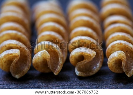 macro shot of wholemeal pasta fusilli from organic whole grain spelt on dark wood, selected focus and extremely narrow depth of field - stock photo