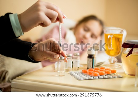 Macro shot of woman filling syringe from ampule with medicines next to patient's bed - stock photo