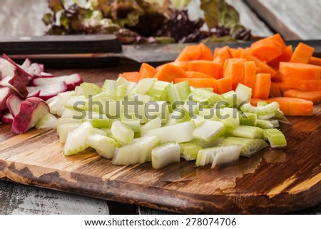 macro shot side view of a bamboo cutting board with chef's knife with freshly chopped organic carrots, lettuce, celery, and radishes - stock photo