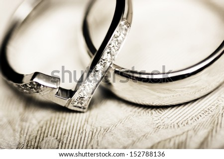 Macro still life photo of a couple of white gold wedding rings with encrusted diamonds on vintage tablecloth background