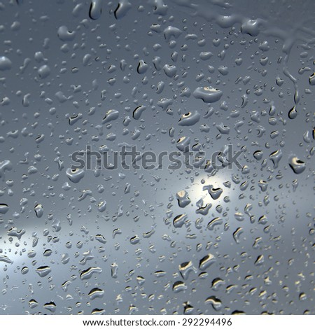 macro texture of raindrops on glass of the car spring - stock photo