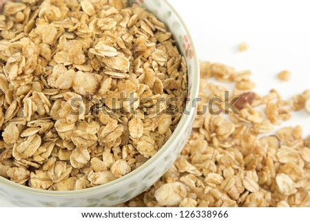Macro top view of a bowl of whole grain granola and oats isolated on a white background - stock photo