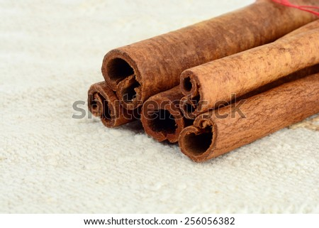 Macro view,close up shot of cinnamon stick on white fiber material like flax  - stock photo