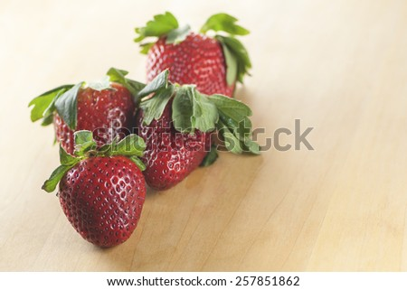 Macro view group of strawberry on a wooden table (Shallow DOF) - stock photo
