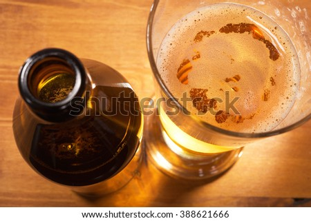 macro view of a beer glass with beer bottle on the table - stock photo