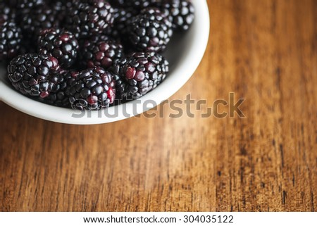 Macro view of a bowl of blackberries, shallow DOF - stock photo