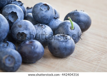 Macro view of a group of blueberries on rustic wooden table, focus on single blueberry, shallow DOF. Tasty blueberries are antioxidant organic superfood.  - stock photo