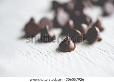 Macro view of a group of succulent chocolate chips on rustic wooden table, shallow DOF - stock photo