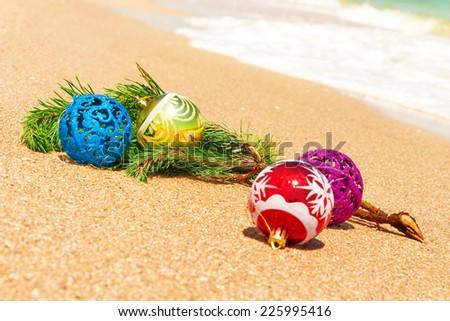 Macro view of christmas balls with fir twig on sand and sea - stock photo