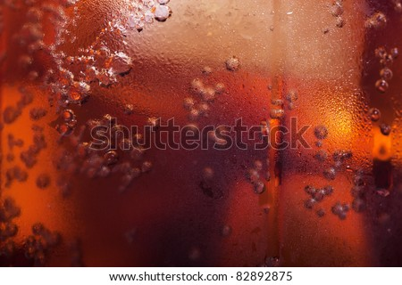 Macro view of cold cola in a glass with ice cubes - stock photo