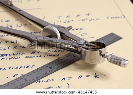 Macro view of drafting compass with steel scale on sheet of yellow paper with computations for general relativity