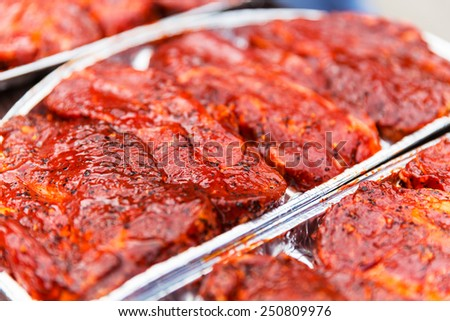 Macro view of fresh raw pork marinated meat with spices and seasonings for barbecue - stock photo