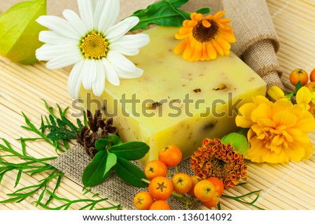 Macro view of natural soap, berries and flowers on the mat - stock photo