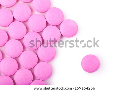 Macro view of pink pills over white background - stock photo