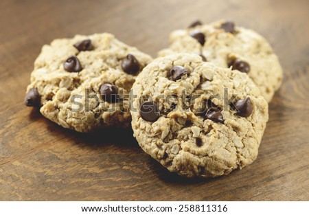 Macro view of three chocolate chip cookies on wooden table (Shallow DOF) - stock photo