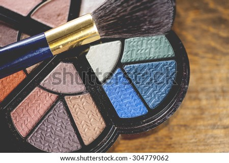 Macro view of vibrant colored cosmetics with brush on rustic wooden table background, shallow DOF - stock photo